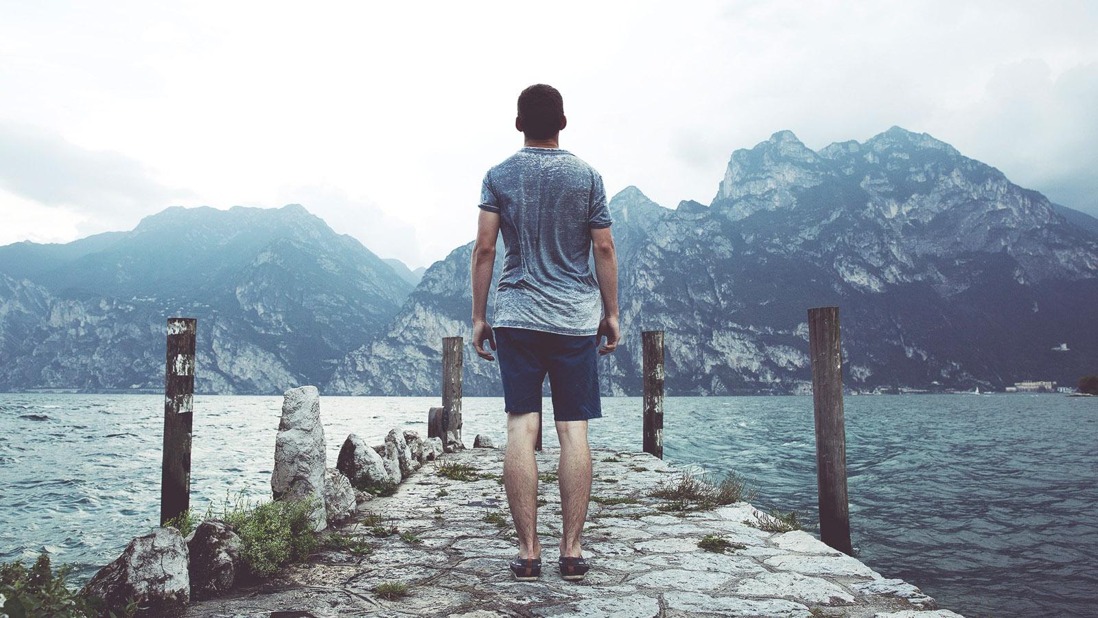 Ragazzo guarda lago da pontile
